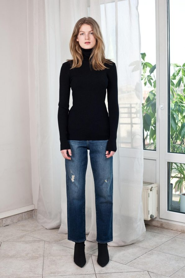 Young woman in black turtleneck and blue jeans, and higheel boots