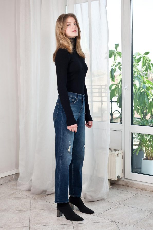 Model wears black fitted ribbed turtleneck sweater and denim jeans